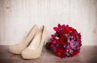 16957626 - beautiful wedding bouquet of red roses and the bride shoes